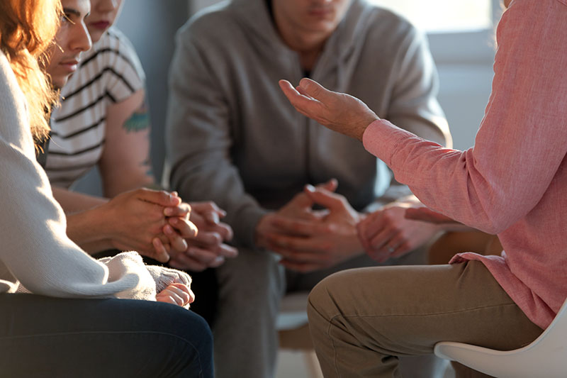 Close-up of a therapist gesticulating while talking to a group.
